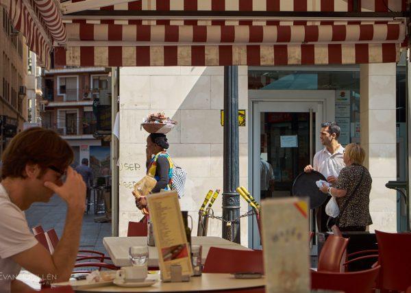 Fotografía de calle. Mujer inmigrante ejerciendo la venta ambulante.