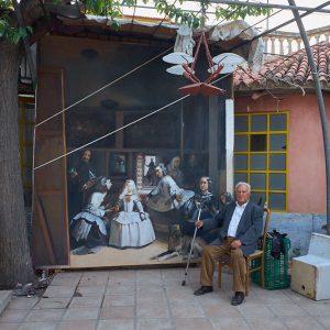 Fotografía de calle. El pintor Miguel Ángel Valverde sentado junto a una réplica de Las Meninas.