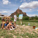 Mujer pintando el castillo de Monteagudo en un cuadro desde la huerta. Un grupo de niños y niñas la observa.