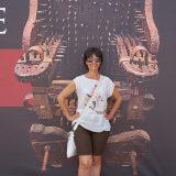 Mujer fotografiada frente al cartel de una silla de tortura.