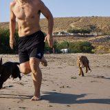Joven jugando con sus perros en la playa.